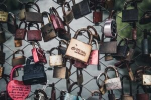 loads of padlocks on a wire fence with the centre one engraved with the word lifetime
