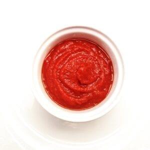 bright red tomato sauce in a white ramekin