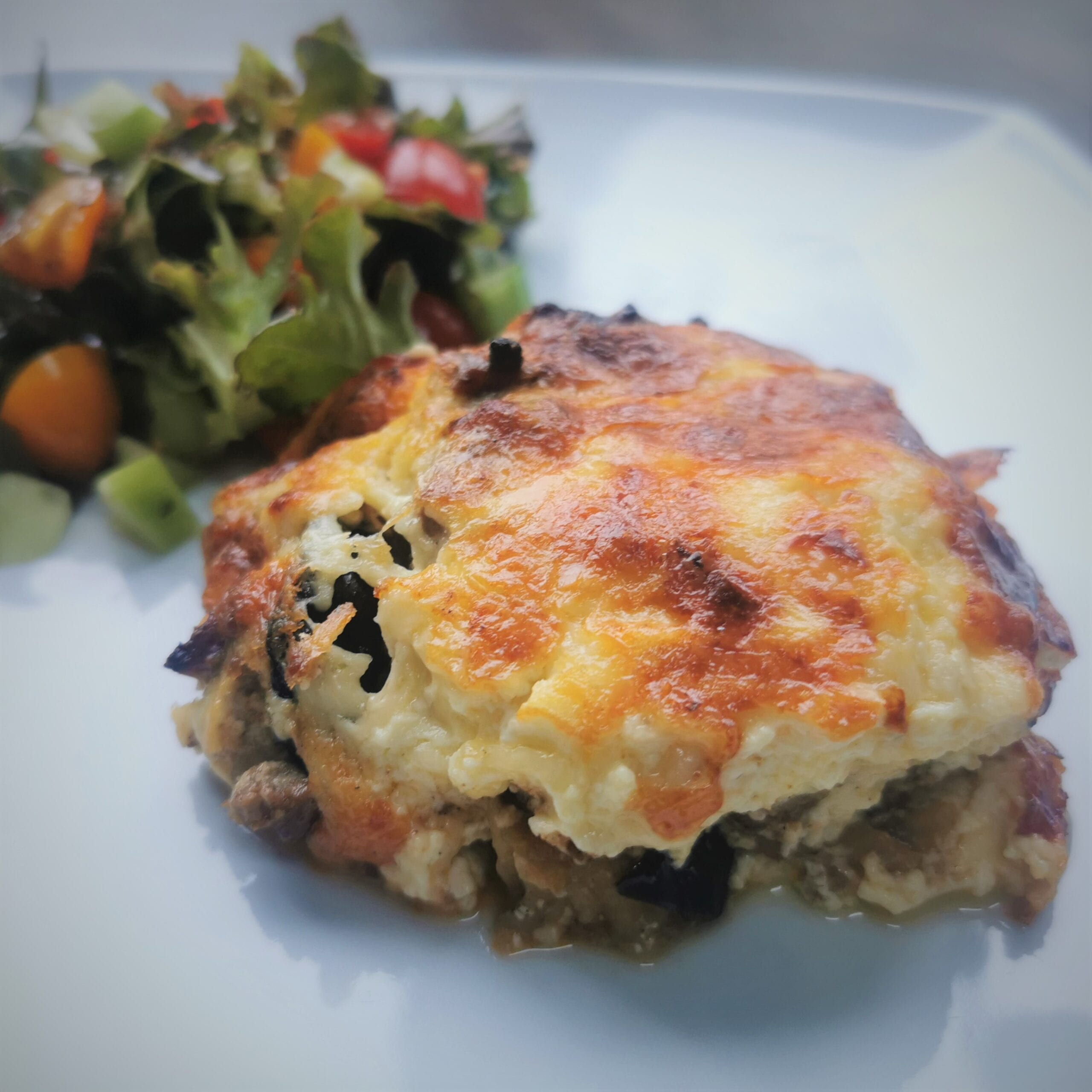 a portion of moussaka with salad in the background