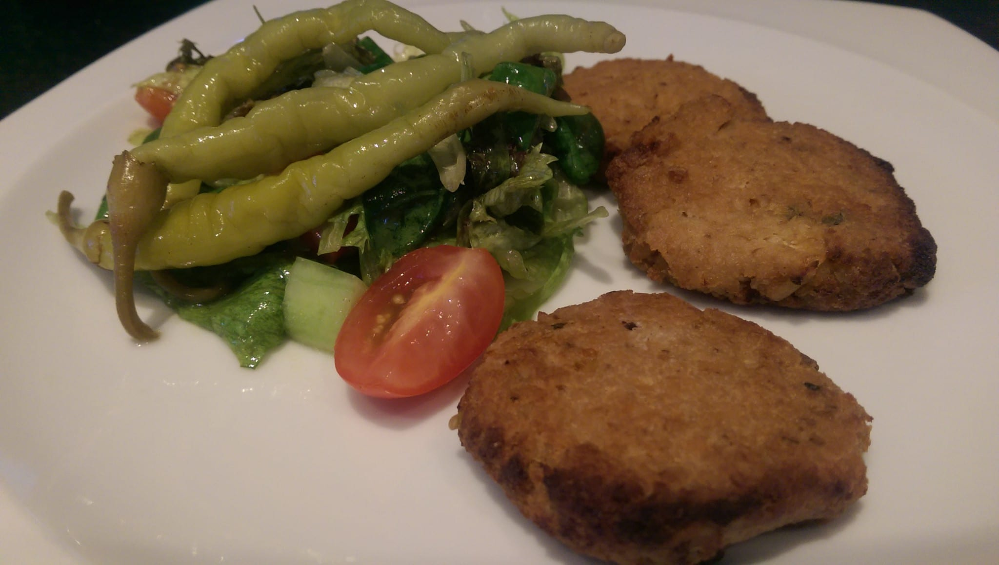 cooked veggie patties with pickled peppers and salad