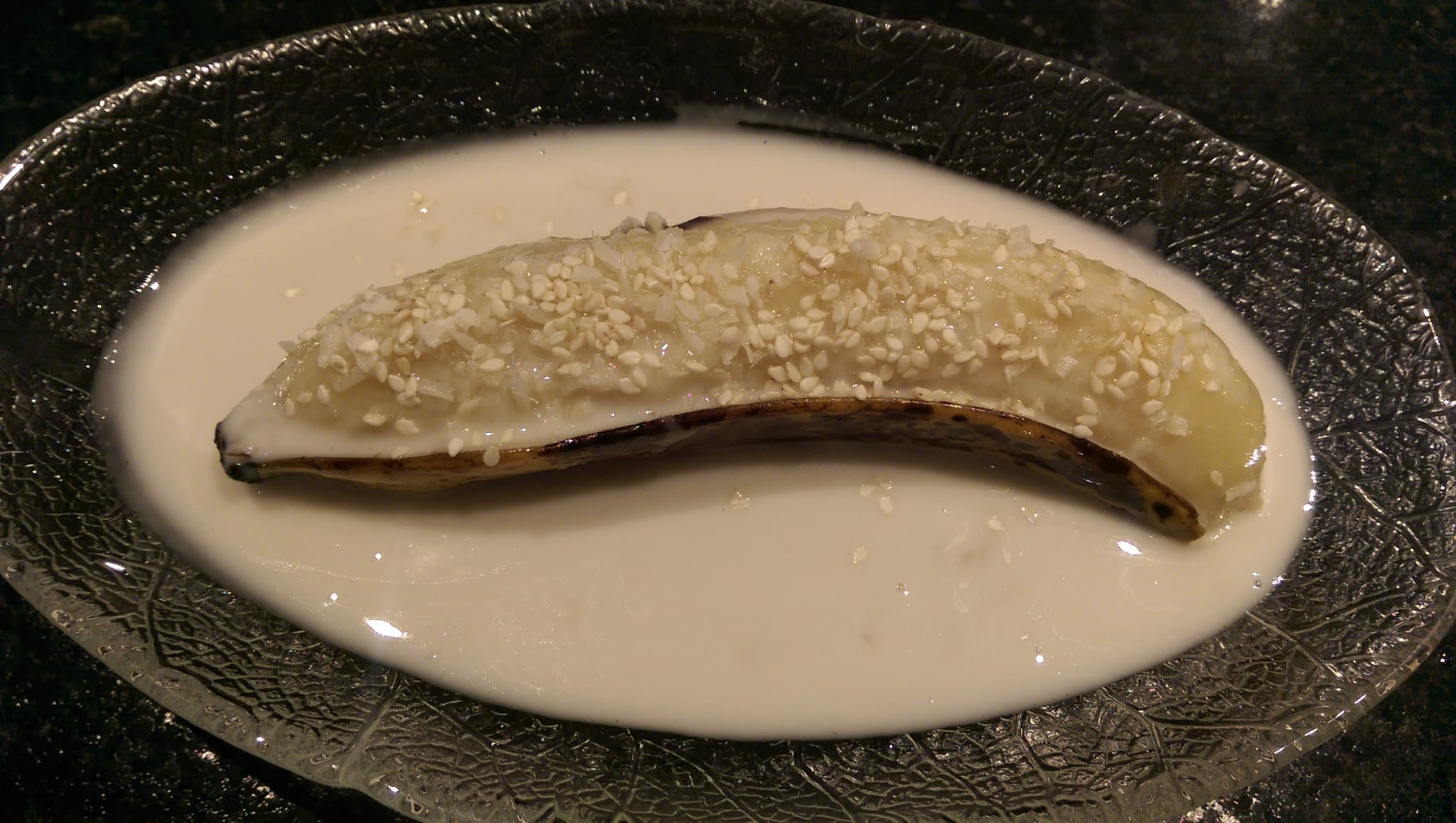 steamed banana with sesame topping in glass bowl