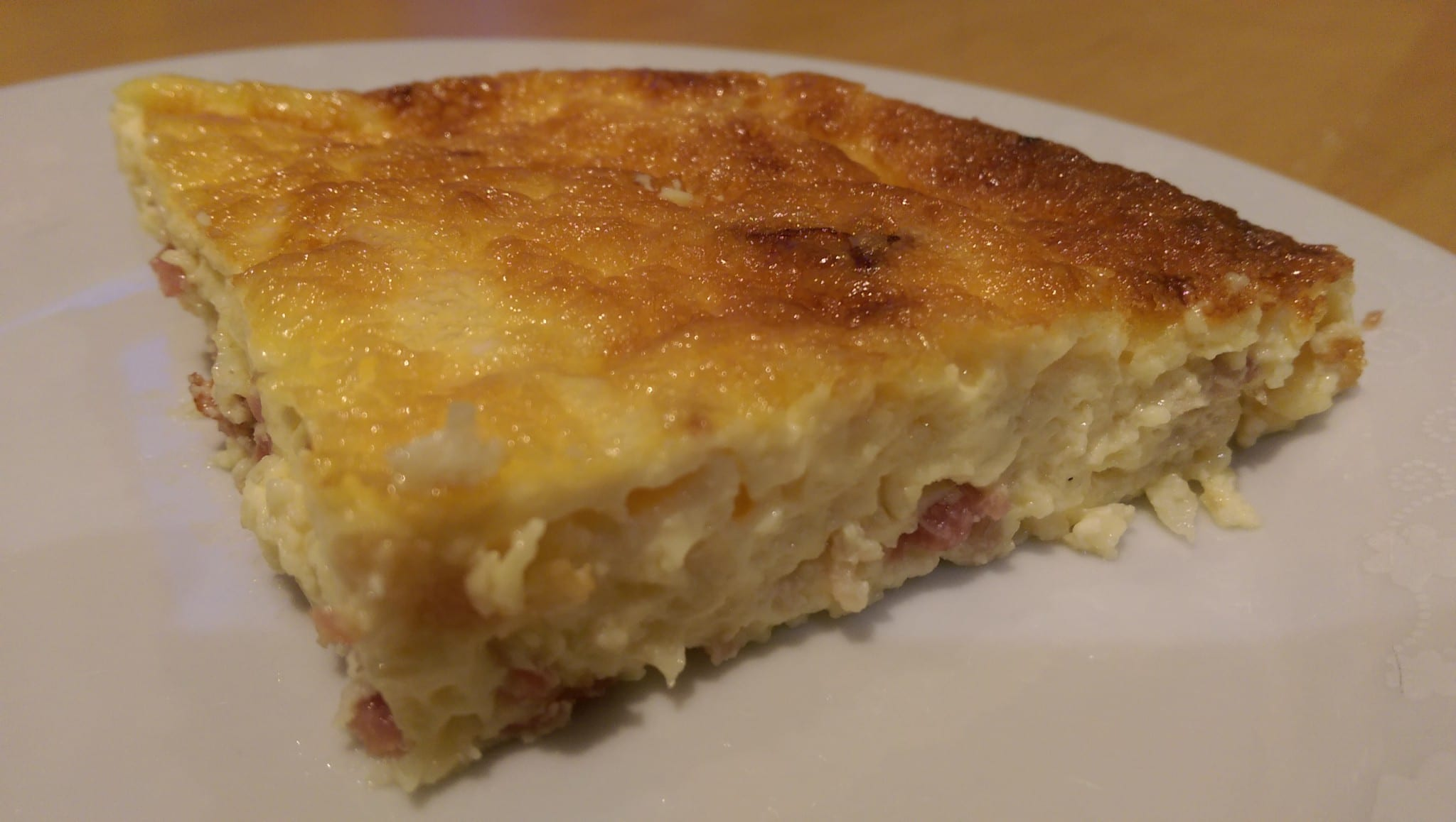 a slice of crustless quiche lorraine