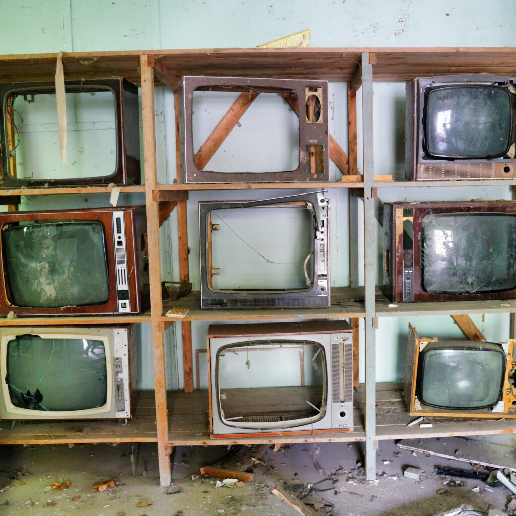 old tvs on a shelving unit with their screens smashed out