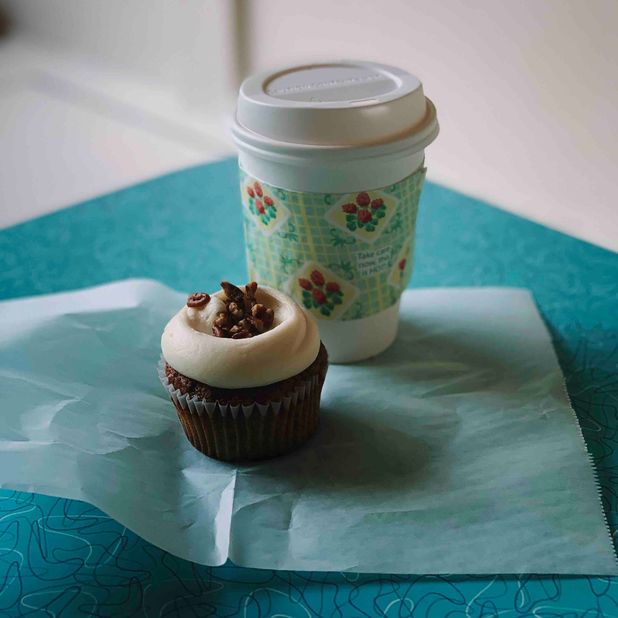 reusable coffee cup and a cupcake on a blue background