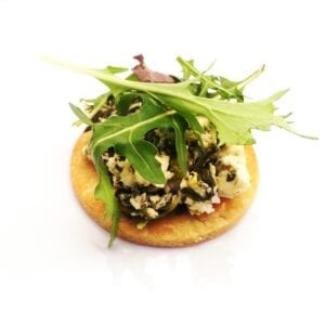 pastry disk with feta and spinach filling on top covered with salad