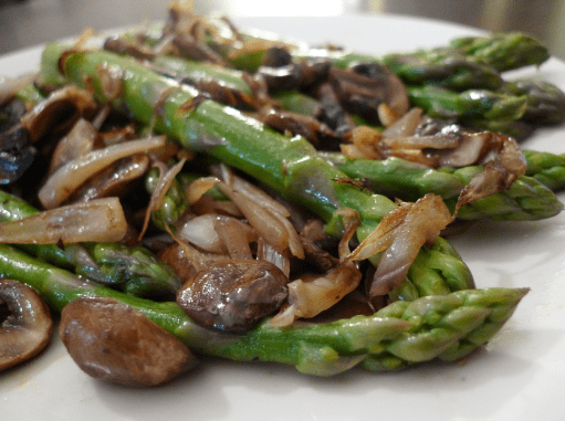 A close up of asparagus, mushrooms and shallots