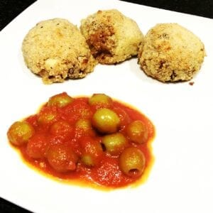 Three arancini balls with olive and tomato sauce