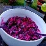 a white bowl with brightly coloured pink coleslaw on an outside table