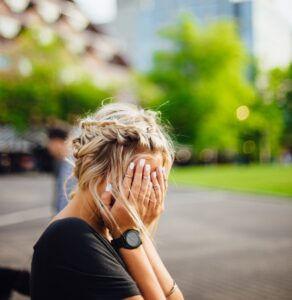 a blonde woman wit her hands covering her face in despair, sitting outside.