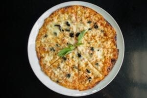 pizza on a plate with a sprig of basil