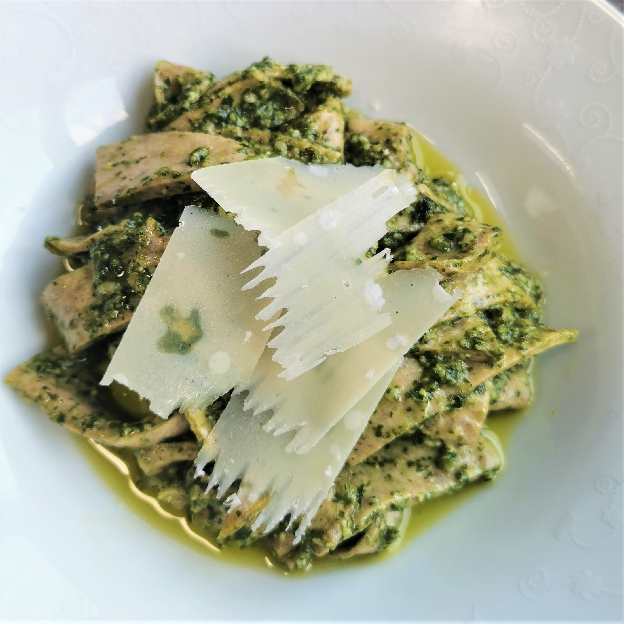 white bowl of low carb pesto pasta with shavings of parmesan in the centre