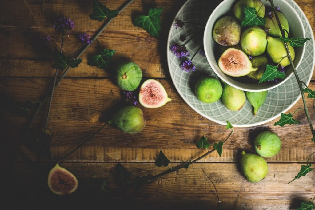 wooden table with fresh figs in a bowl and strewn artfully