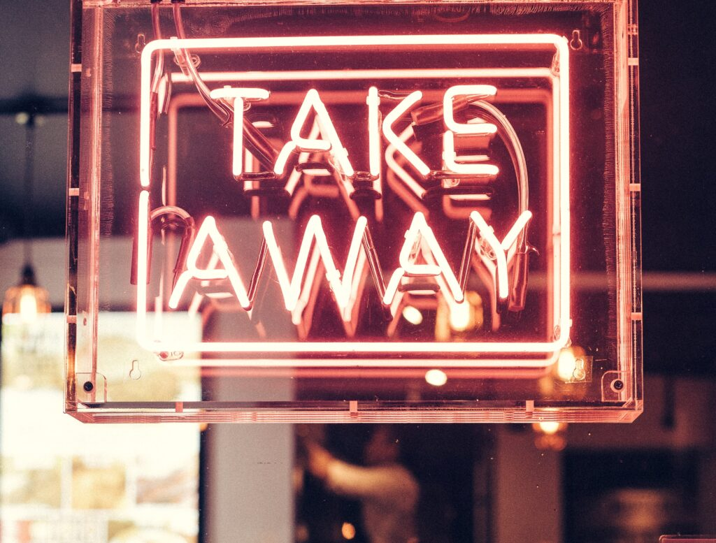 neon sign in a restaurant window saying take away