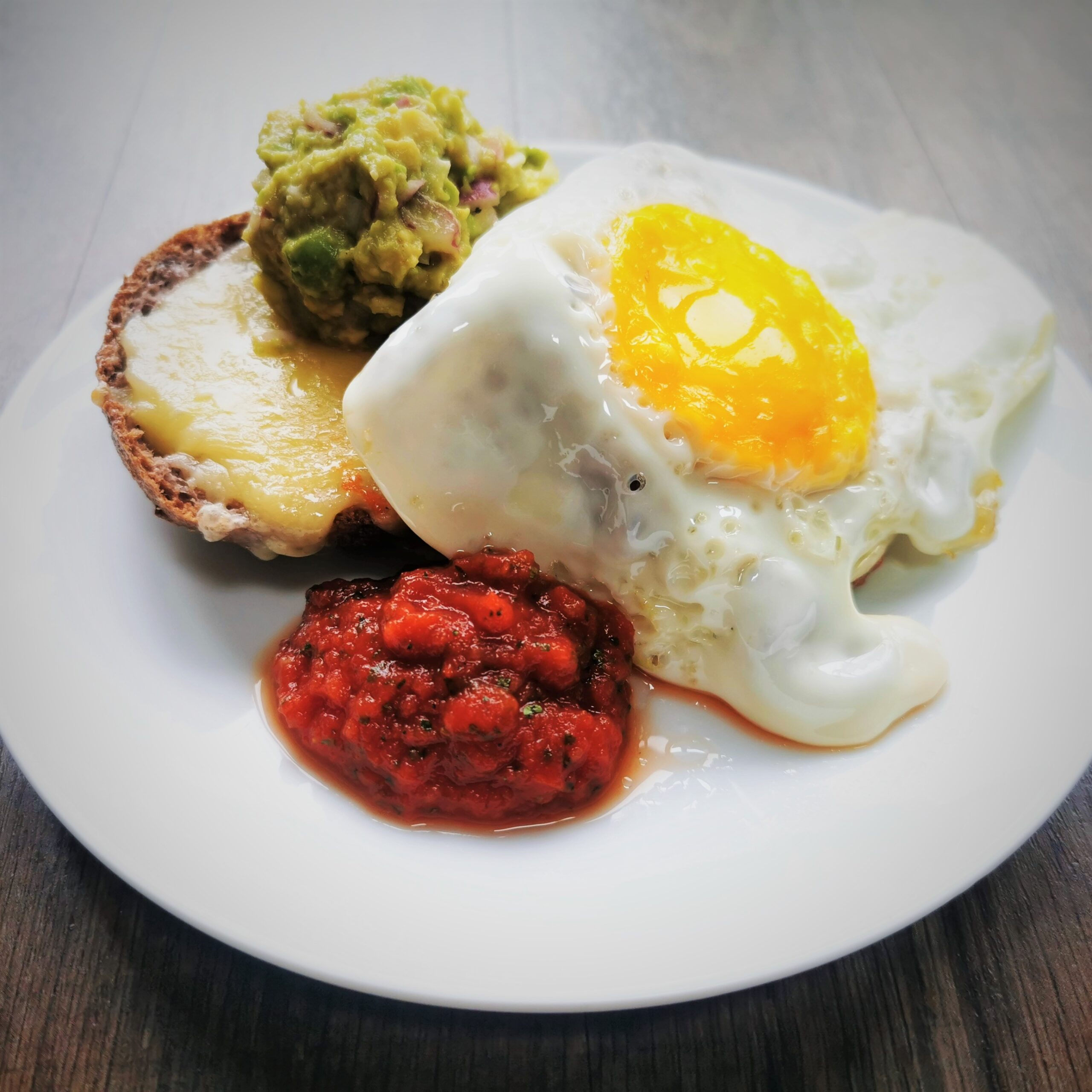 Golden yolked fried egg on a low carb roll with salsa and guacamole on a white plate placed on a wooden surface