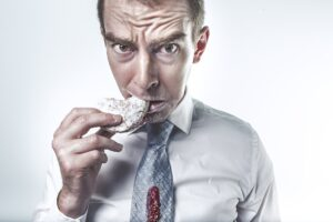 worried man eating a donut with jam spilled on his tie