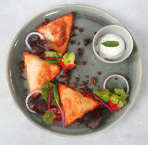 grey plate on a white background with 3 lamb samosas, a bowl of mint yoghurt and salad garnish