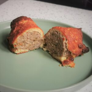 a low carb sausage roll cut in half on a green plate with a white kitchen surface