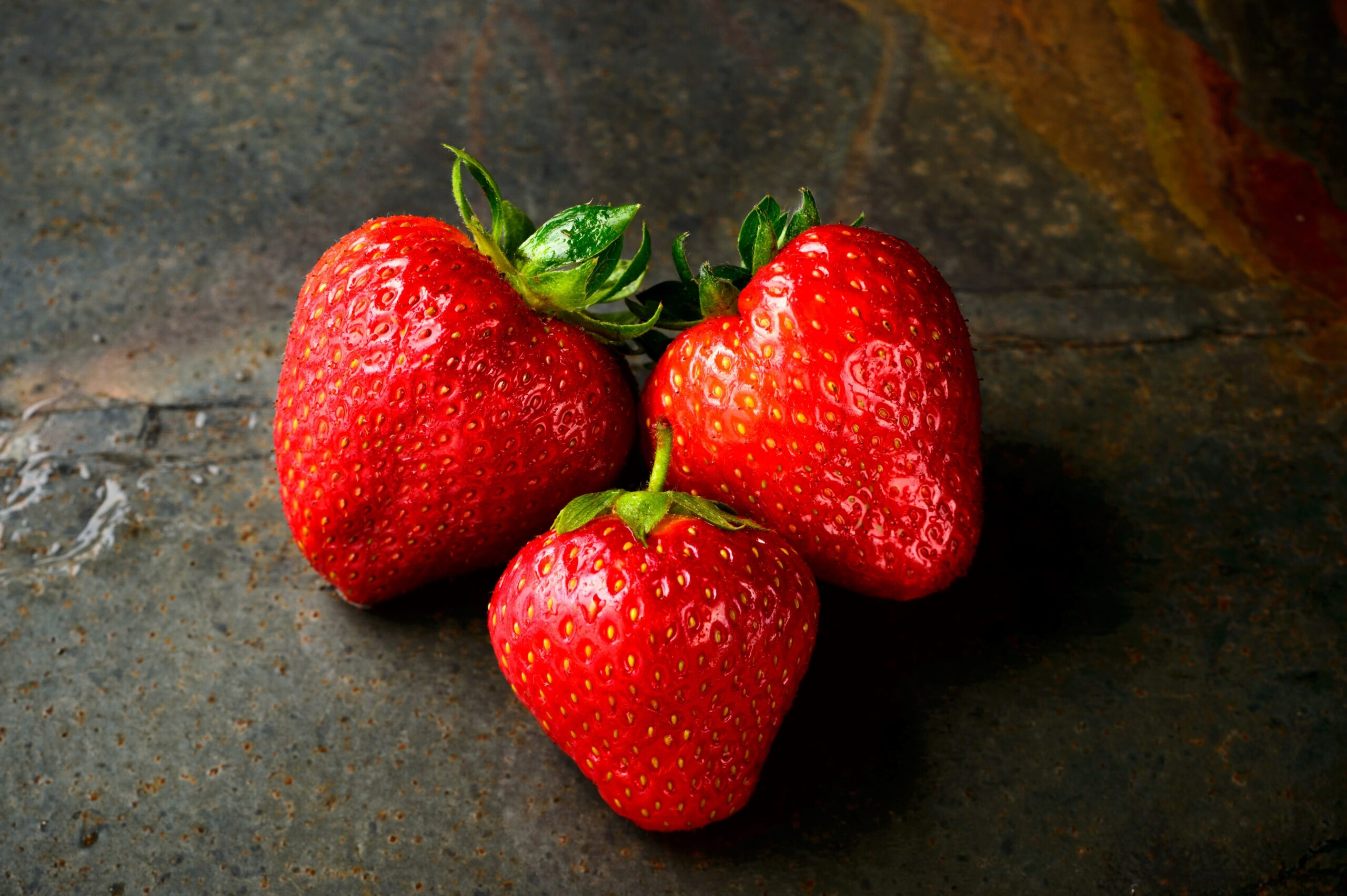 three strawberries on a grey surface
