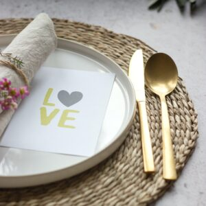 A rafia placemat with a white plate upon which is a card saying love, a napkin with flowers as a napkin ring and a gold knife and spoon.