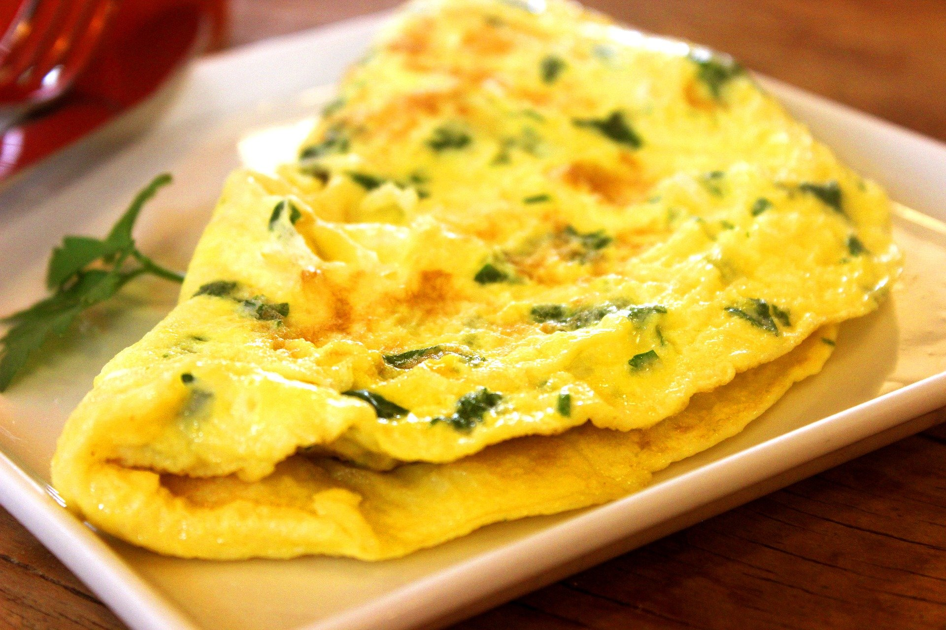 A square white plate with a folded egg omelette with herbs