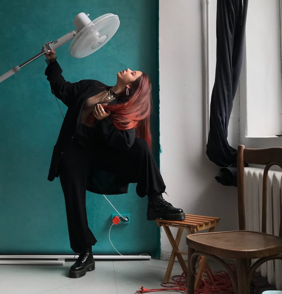 a woman in black, striking a pose, holding an electric fan to her face in front of a blue wall by a window