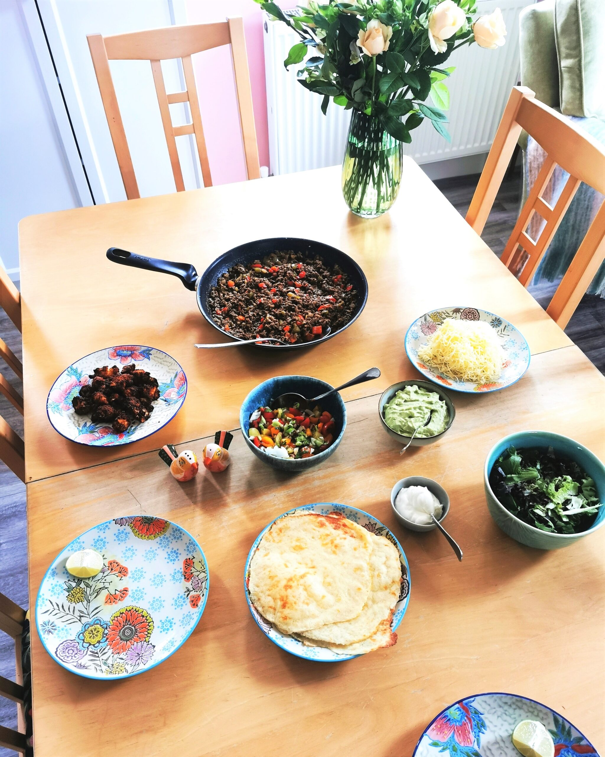 A wooden table laid with colourful plates, a pan of mexican meat, guacamole, creme fraiche, grated cheese, salsa, roasted cauliflower and salad. There is also a vase with flowers.