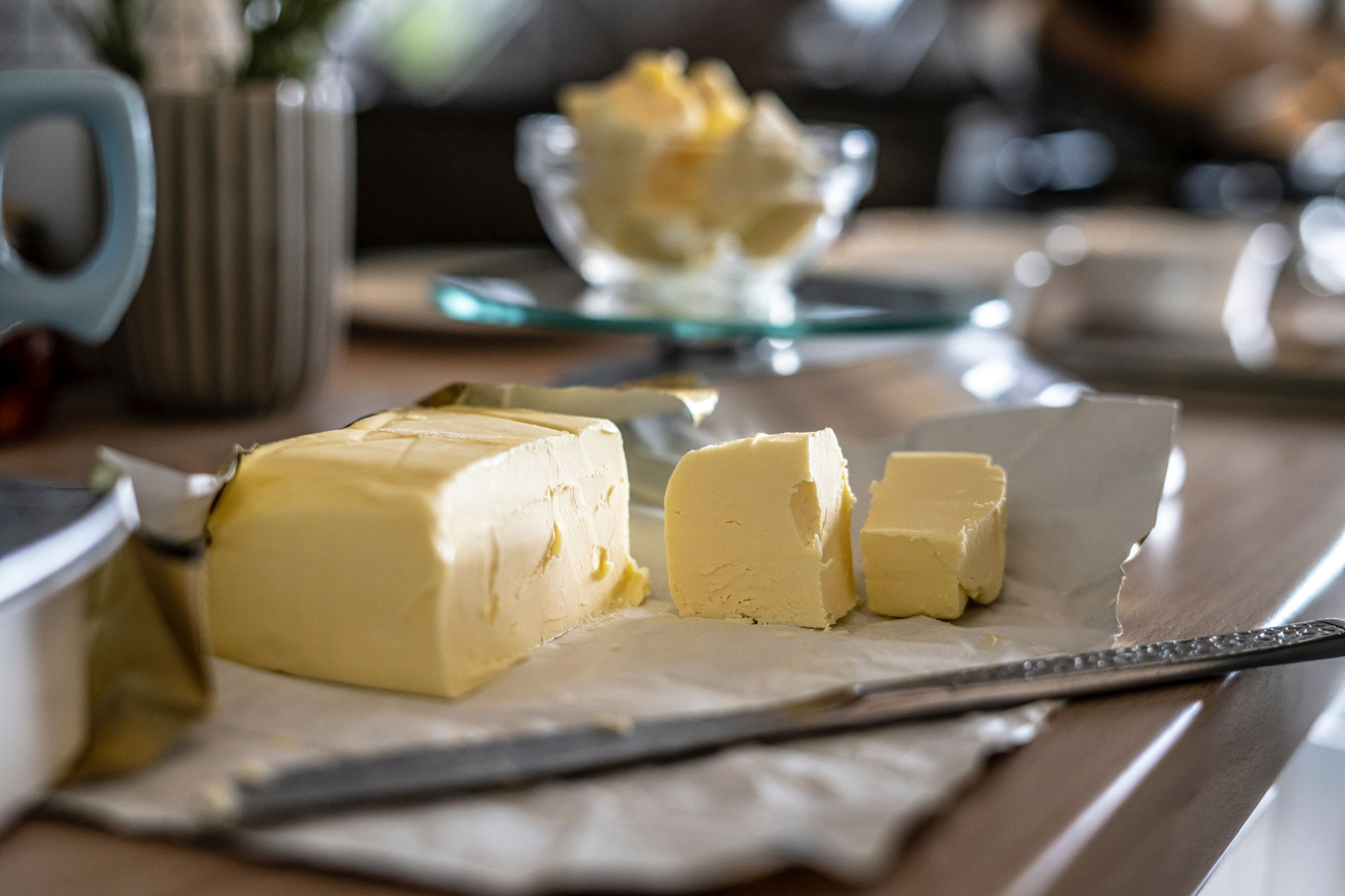 butter on a white plate cut into slices with a knife in the foreground