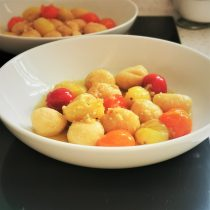 Two white bowls of gnocchi, one in front of the other. Balls of gnocchi with red, orange and yellow baby plum tomatoes with garlic butter and oil. The background is black