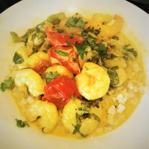 prawn curry with tomatoes and spinach and a vibrant yellow sauce