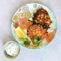 floral plate on a mottled background with two onion bhaji, a lemon wedge, a sprig of coriander and a small bowl of mint yoghurt